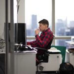 An employee working at the computer in the PDT Partners office